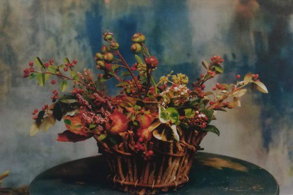 composizione artistica di fiori e ramoscelli all'interno di un cestino di vimini