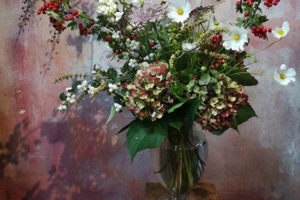 Vaso di fiori con fiori bianchi e bacche rosse